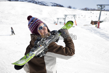 woman carrying skis
