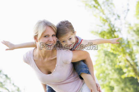 woman giving young girl piggyback ride