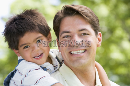 man and young boy embracing outdoors