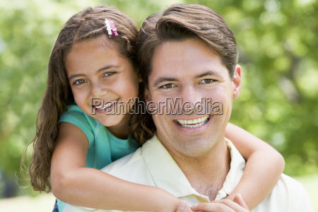 man and young girl embracing outdoors