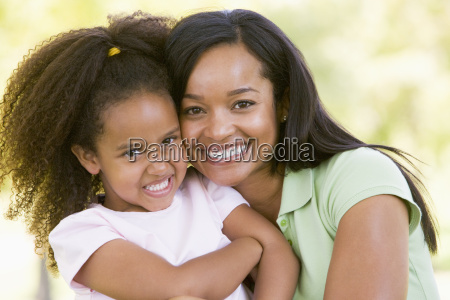 woman and young girl outdoors embracing