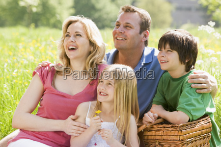 family sitting outdoors with picnic basket