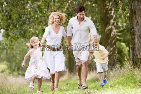 family running on path holding hands