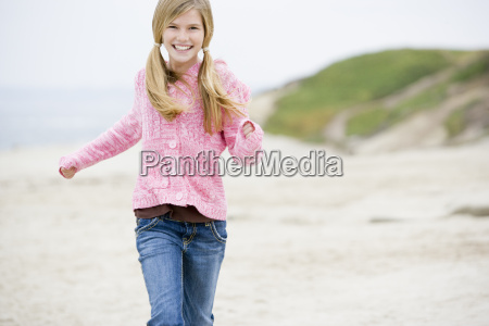 young girl running at beach smiling