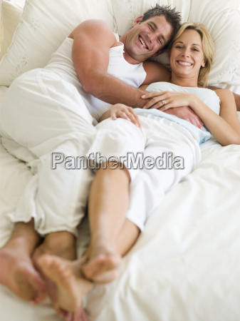 couple lying in bed smiling