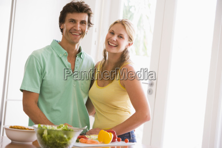 couple in kitchen cutting up vegetables