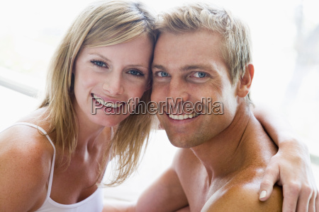 couple in bedroom embracing and smiling