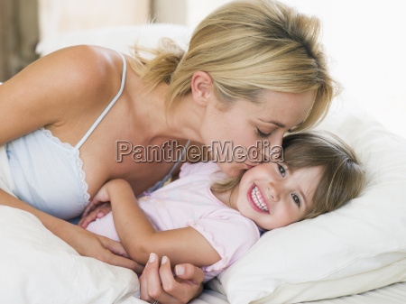 woman kissing young girl in bed