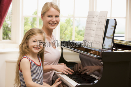 woman and young girl playing piano