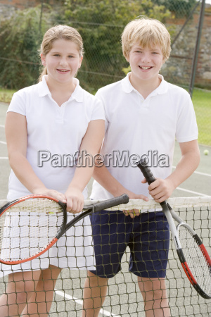 two young friends with rackets on
