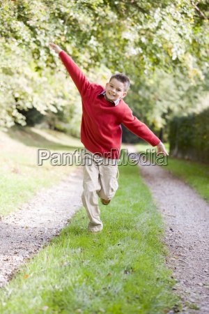 young boy running on a path
