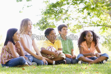 five young friends sitting outdoors with