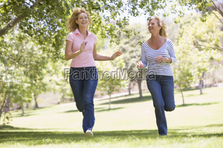 two women running in park and