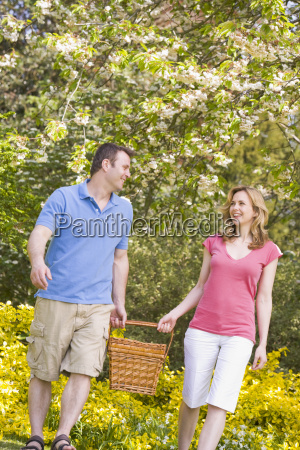couple walking outdoors with picnic basket