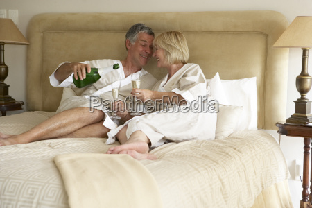 middle aged couple enjoying champagne in