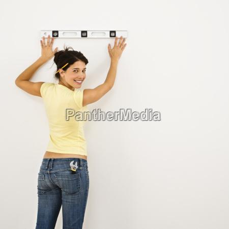 woman leveling wall