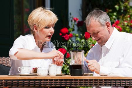 aelteres paar beim kaffee auf veranda