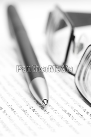 open book with eyeglasses and pen