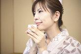 japanese woman putting on kimono