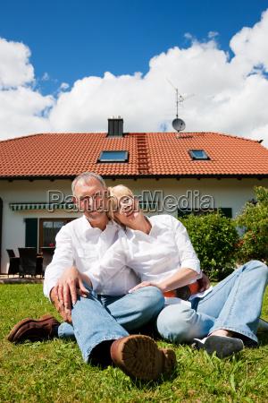 aelteres paar sitzt vor eigenheim