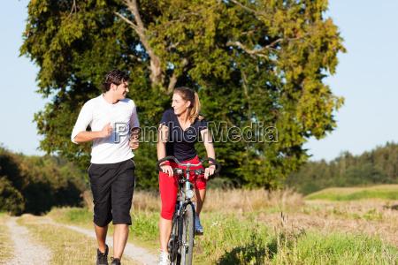 sport paar joggt und faehrt fahrrad