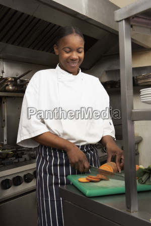 female chef preparing vegetables in restaurant