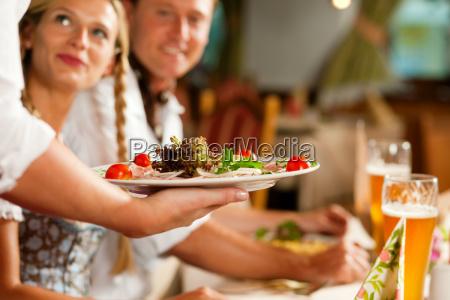 kellnerin serviert in bayerischem lokal