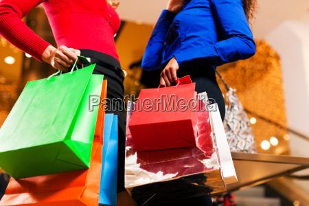 zwei frauen beim shopping im kaufhaus