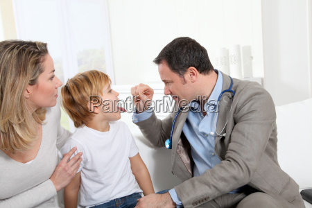 doctor examining little boy throat