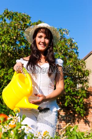 gartenarbeit im sommer frau giesst