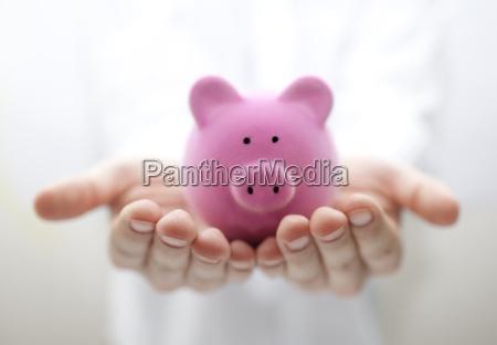man holding piggy bank shallow dof