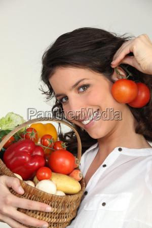 brunette holding basket of vegetables