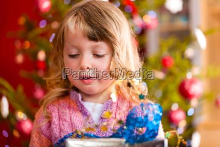 weihnachten kleines maedchen mit weihnachtsgeschenk