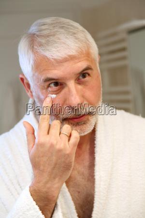 portrait of senior man applying moisturizing