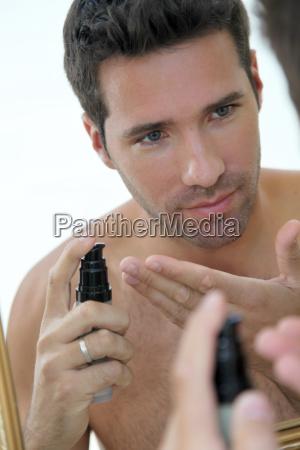 handsome man applying moisturizer in front