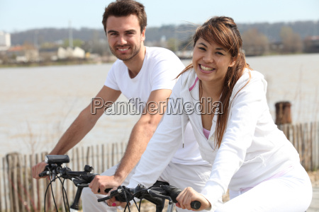 young couple doing bike near the