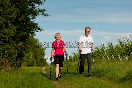 glueckliches aelteres paar beim nordic walking