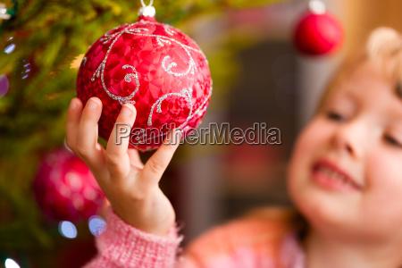 familie schmueckt weihnachtsbaum