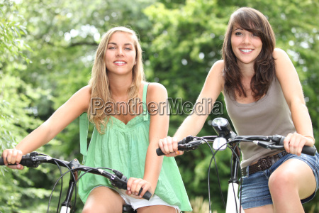 two teenage girls riding bikes in