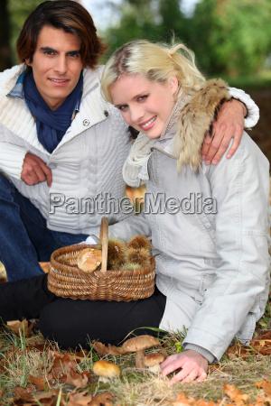 couple gathering mushrooms in basket