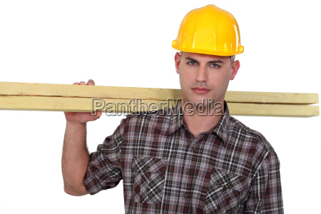 carpenter carrying planks of wood