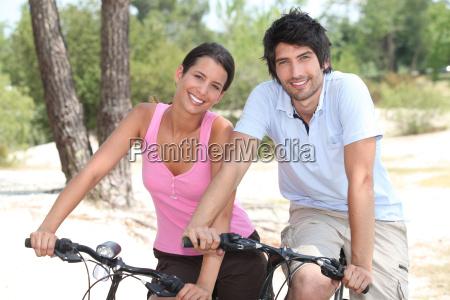 couple cycling through a coastal pine