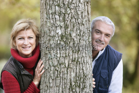 married couple leaning against tree