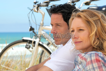 couple with bicycles by the coast