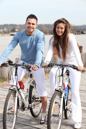 young couple riding bikes along a