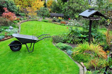 gartenarbeit mit schubkarre im herbstgarten