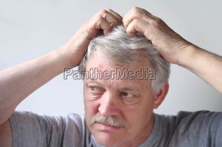 senior scratches his head