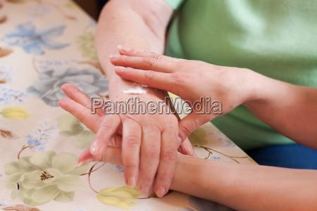 altenpflegerin cremt seniorin die hand