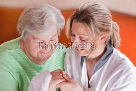altenpflegerin waescht seniorin die haende