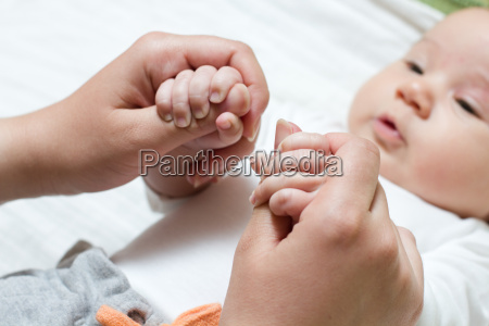 baby holding mother hand